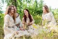 Beautiful women relaxing on nature attractive in traditional russian clothes at background ivan kupala holiday celebration Stock Photo
