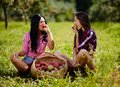 Beautiful women taking a bite of an apple sexy sitting near baskets apples Stock Images