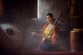 Beautiful women in traditional dress costume playing treble fiddle. Treble fiddle or soprano sounded string Thai music instrument