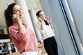 Beautiful women using phones and talkin during break colleagues Royalty Free Stock Image