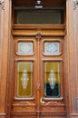 Beautiful wooden antique double entrance doors with glass rectangles with white painted floral ornaments