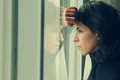 Beautiful year old woman stands in front of the window Royalty Free Stock Photos
