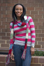 Beautiful young adult african american woman posing outdoors against brick wall wearing scarf, colorful autumn sweater