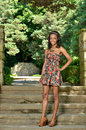 Beautiful young african american woman in floral sundress stunning standing on steps garden wearing a short dress smiling portrait Royalty Free Stock Photography