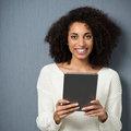 Beautiful young african american woman with a lovely friendly smile standing against a grey studio background holding a tablet Royalty Free Stock Image