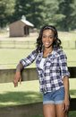Beautiful young african american woman standing along farm fence rural stunning in country western attire a wooden on a country Stock Photography