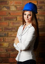 Beautiful young architect adult caucasian woman wearing a blue safety hat black pants and a white shirt in front of a brown brick Stock Photos