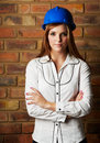 Beautiful young architect adult caucasian woman wearing a blue safety hat black pants and a white shirt in front of a brown brick Royalty Free Stock Photo