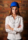 Beautiful young architect adult caucasian woman wearing a blue safety hat black pants and a white shirt in front of a brown brick Royalty Free Stock Images
