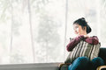 Beautiful young Asian girl relaxing at home, sitting alone by window, looking at copy space Royalty Free Stock Photo