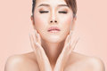 Beautiful young asian woman with closed eyes touching her face Royalty Free Stock Photo