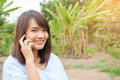 Beautiful young asian woman who talks on telephone the Stock Photography