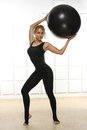 Beautiful young attractive beautiful woman with blond hair standing holding up ball for fitness black dressed up in black suit e Royalty Free Stock Photo
