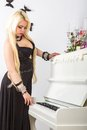 Beautiful young attractive woman in evening dress and piano a light room Royalty Free Stock Images