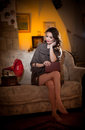 Beautiful young bare feet woman sitting on sofa holding a book having a red gramophone near her vintage scenery attractive Royalty Free Stock Image
