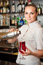 Beautiful young barmaid making cocktail Stock Image