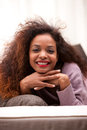Beautiful young black happy woman on a sofa in her living room Stock Images