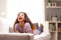 Beautiful young black happy woman on a sofa in her living room laughing Stock Photo