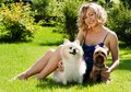 A beautiful young blond girl in the park with dogs summer Royalty Free Stock Photo