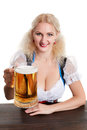 Beautiful young blond girl in traditional costume drinks out of oktoberfest beer stein.