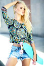 Beautiful young blond model girl in summer hipster clothes with skateboard high fashion look glamor stylish sexy bright casual Royalty Free Stock Images