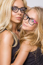 Beautiful young blond mom of an adorable little baby girl with long hair in black glasses snuggling and looking the lens