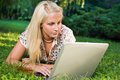 Beautiful young blond using laptop in nature. Royalty Free Stock Photo