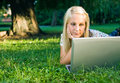 Beautiful young blond using laptop in nature. Stock Photos