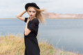 Beautiful young blond woman in a black dress and a light black hat in the desert and the wind blowing her hair in a hot summer day Royalty Free Stock Photo