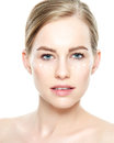 Beautiful Young Blond Woman with Face cream applied under her eyes. Facial treatment. Beauty and spa concept.