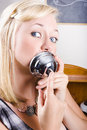 Beautiful young blond woman holding service bell to face depiction lip service Royalty Free Stock Image