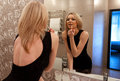 Beautiful young blond woman putting on makeup in the bathroom Royalty Free Stock Photo