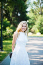 Beautiful young blond woman in a white dress outdoors Royalty Free Stock Photo