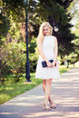 Beautiful young blond woman in a white dress outdoors Stock Photos