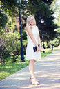 Beautiful young blond woman in a white dress outdoors Royalty Free Stock Image