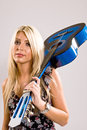 Beautiful young blonde female holding a blue guitar over her shoulder in floral print dress and look of attitude on her face Royalty Free Stock Photo
