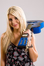 Beautiful young blonde female holding a blue guitar over her shoulder in floral print dress with smile on her face Stock Photos