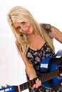 Beautiful young blonde female playing a guitar blue in floral print dress Stock Images