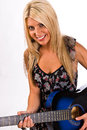 Beautiful young blonde female playing a guitar blue in floral print dress Royalty Free Stock Image
