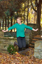 Beautiful young blonde woman autumn jumping for joy over path with brightly colored leaves wearing a green shirt black yoga pants Stock Photography