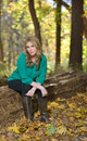 Beautiful young blonde woman autumn sitting on a log among fallen leaves wearing a green shirt black yoga pants and boots Stock Image
