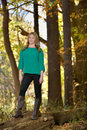 Beautiful young blonde woman autumn standing on a log among fallen leaves wearing a green shirt black yoga pants and boots Royalty Free Stock Photos
