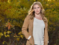 Beautiful young blonde woman autumn stunning in beige colored sweater jacket and blue jeans standing outside in sun highlighting Stock Photography