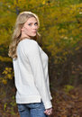 Beautiful young blonde woman autumn stunning in beige colored sweater standing outside in sun highlighting her hair looking back Royalty Free Stock Photo