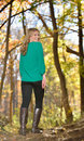 Beautiful young blonde woman autumn walking on a log among fallen leaves wearing a green shirt black yoga pants and boots Stock Images