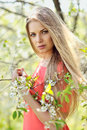 Beautiful young blonde woman standing near blooming tree Royalty Free Stock Photo
