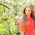 Beautiful young blonde woman standing near blooming tree copys Stock Images