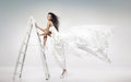 Beautiful young bride holding the ladder white Stock Photo