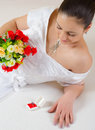 Beautiful young bride lying on the bed and looking at her wedding ring Royalty Free Stock Photo