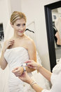 Beautiful young bride with mother looking at price tag of bracelet in bridal store Stock Photos